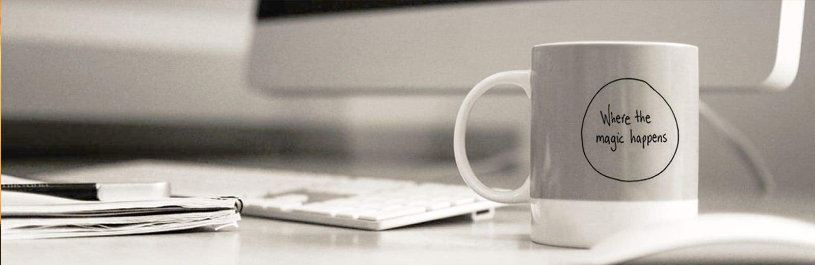 A photo of a desk with a iMac and a mug with the text: